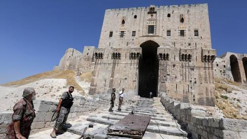 Syrian government forces stand next to the blown-up gate of Aleppo's historical citadel, also known as Crac Des Chevaliers