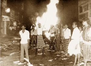 A croud cheering in pleasure after setting fire to Tamil shops