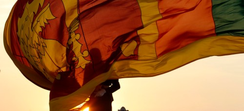 An air force officer holds Sri Lanka's national flag as the sun sets at Galle Face Green in Colombo February 2, 2013. Sri Lankans will celebrate the country's 65th Independence day on February 4 .REUTERS/Dinuka Liyanawatte (SRI LANKA - Tags: POLITICS ANNIVERSARY MILITARY) - RTR3D9I2