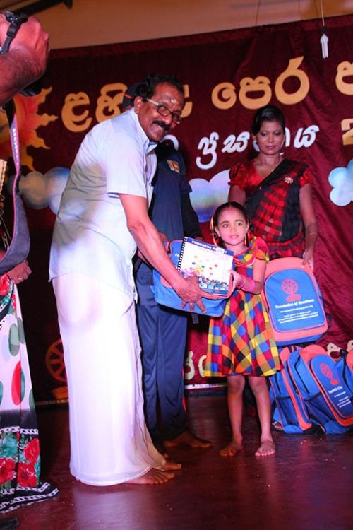 Honourable Minister Gurukalarajah presents school bags to younf children from the FoG Lahiru Pre-School