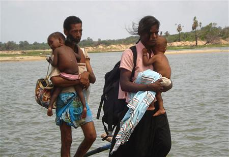 In this photograph released by the Sri Lankan navy April 22, 2009, a Tamil man and woman carry children after fleeing an area called the 'No Fire Zone' controlled by the Liberation Tigers of Tamil Eelam (LTTE), in northern Sri Lanka. REUTERS/Sri Lankan Government/Handout